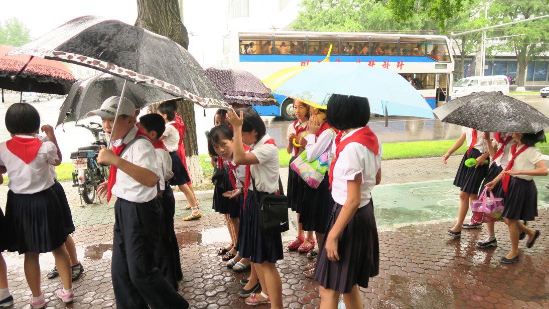Niños paseando bajo la lluvia.